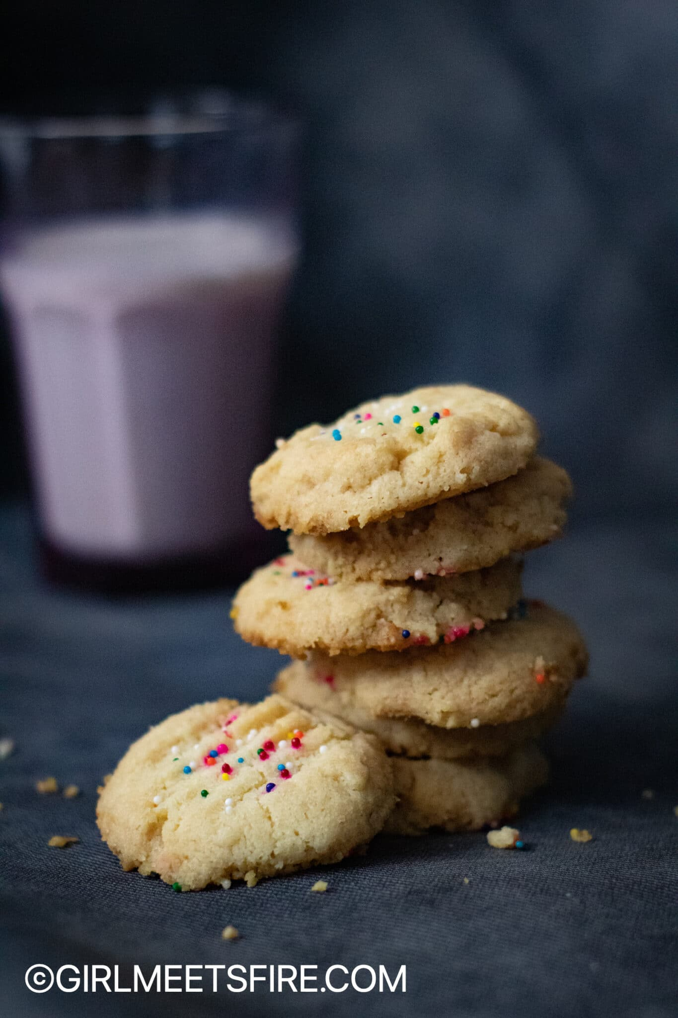 a stack of sprinkled polvorones with a glass of milk on the background