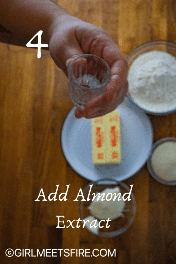 a shot glass with a teaspoon of almond extract to be added to the batter